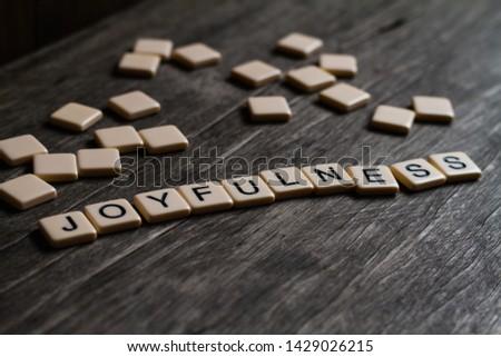 Joy/Joyfulness/Joyful spelt out using tiles on a timber surface #1429026215