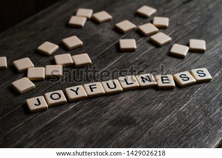 Joy/Joyfulness/Joyful spelt out using tiles on a timber surface #1429026218