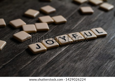 Joy/Joyfulness/Joyful spelt out using tiles on a timber surface #1429026224