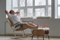 Joy of life. Total relaxation. Handsome young man keeping eyes closed and holding hands behind head while sitting in big comfortable chair at home
