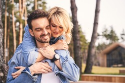 Joy of love. Loving blonde young woman clasping her happy handsome boyfriend in her arms