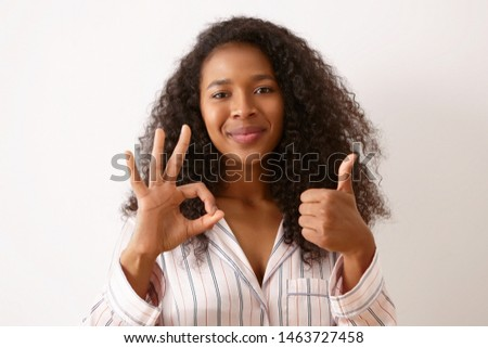 Joy, positiveness and body language. Beautiful happy young girl with curly black hair posing isolated dressed in silk pajamas, making thumbs up gesture and showing ok sign, smiling Stock photo ©