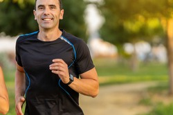 Joyful adult man working out in the park and jogging. He is smiling and looking at front.