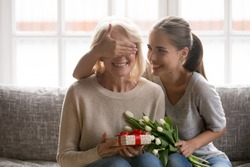 Joyful adult millennial daughter covering happy mommys eyes, holding flowers bunch, sitting together on sofa. Carrying young woman prepared surprise gift for mature mother for birthday celebration.