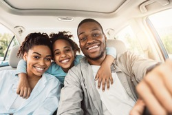Joyful African American Family Hugging Sitting In Car During Summer Road Trip. Parents And Daughter Posing In New Auto Smiling To Camera. Transportation, New Automobile Concept