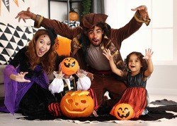 Joyful african american family parents and children in Halloween costumes making scary gesture and smiling at camera while sitting on with jack-o-lantern on floor, celebrating all hallows day