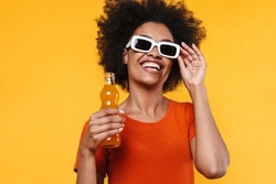 Joyful african american girl in sunglasses drinking soda and laughing isolated over yellow background