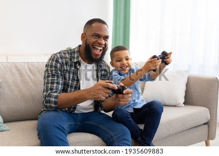Joyful African Father And Kid Boy Playing Videogames At Home