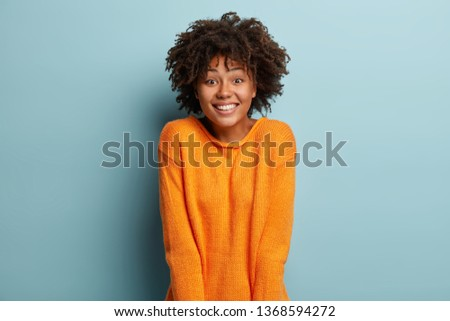 Joyful Afro American girlfriend gets unexpected surprise from boyfriend, has broad smile, feels pleased, wears orange jumper, expresses nice emotions, isolated over blue background. Facial expressions