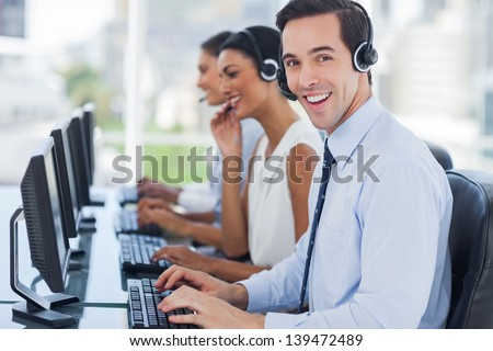 Joyful agent working in a call centre with his headset