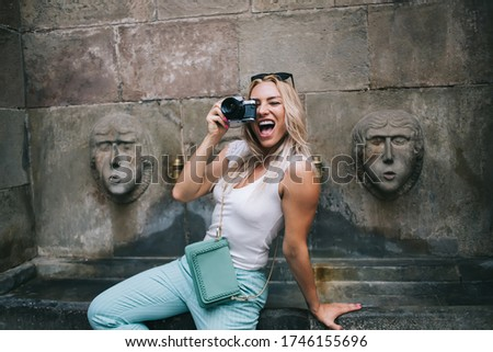 Photo of Joyful amateur satisfied with journey travel for photographing beautiful city landscape with ancient architecture buildings, happy woman with old fashioned technology making photo pictures