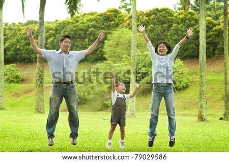 Joyful Asian family jumping together in the park