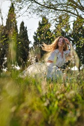 Joyful attractive female wearing sundress touching flying hair gently while spending sunny day on grassy verdant glade in summer countryside