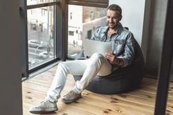 Joyful attractive guy is laboring on computer