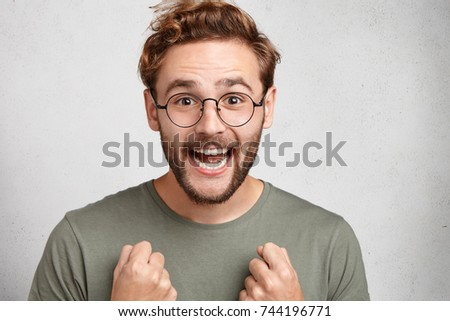 Joyful attractive male wonk rejoices taking part in knowledge contest, being sure at his victory, smiles happily, demonstrates white even teeth. Satisfaction, emotions, happiness and success concept
