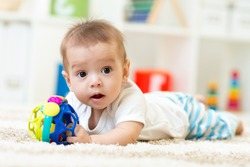 Joyful baby kid lying on the carpet with toy in nursery room