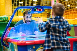 Joyful bearded father and son playing air hockey game at amusement park