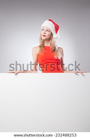 Joyful Beautiful christmas woman in santa hat holding empty board isolated on white background
