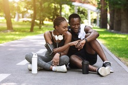 Joyful black couple resting after jogging in park, checking smartwatch fitness tracker while sitting on path, enjoying training outdoors, free space