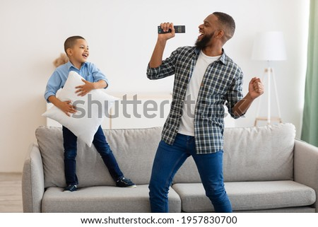 Joyful Black Dad And Little Son Singing And Dancing Together Celebrating Father's Day At Home. Happy Kid Boy Having Fun With Daddy Having Domestic Party With Karaoke. Joy Of Fatherhood Concept