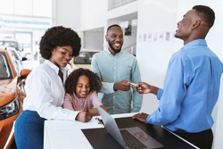 Joyful black family giving credit card to car salesman, paying for new auto at dealership store. African American customers purchasing automobile, signing agreement at showroom