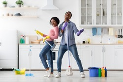 Joyful black loving couple singing songs while cleaning kitchen, using broom and mop as microphones and guitar, cheerful african american young man and woman imitating rock stars while house-keeping