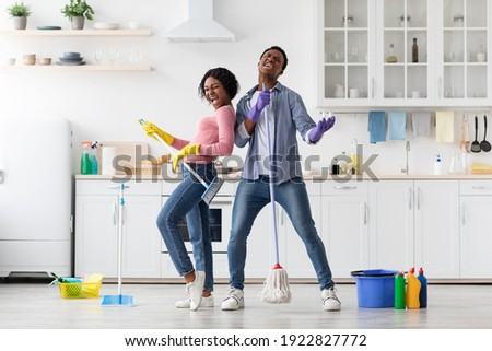 Joyful black loving couple singing songs while cleaning kitchen, using broom and mop as microphones and guitar, cheerful african american young man and woman imitating rock stars while house-keeping Zdjęcia stock ©