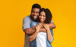 Joyful black sweethearts hugging and posing to camera, standing together over yellow background in studio, copy space