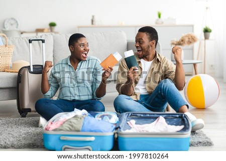 Joyful Black Tourists Couple Holding Tickets And Shaking Fists Celebrating Vacation Packing Suitcase At Home. Happy Tourists Preparing For Journey. Summer Tourism Concept. Selective Focus