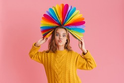 Joyful blonde girl grimacing while posing with multicolored fan on her head isolated over pink background