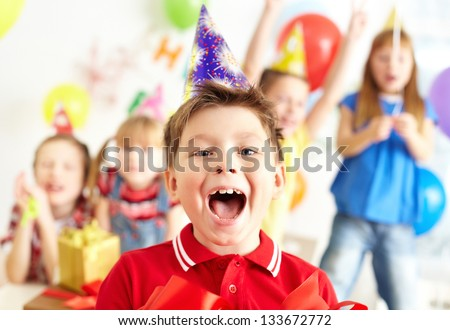 Joyful boy looking at camera with his friends on background