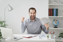 Joyful business man in gray shirt sit at desk work on laptop pc computer in light office on white wall background. Achievement business career concept. Hold fan of cash money doing winner gesture