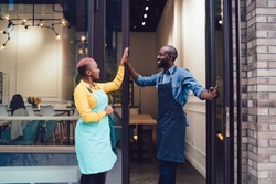 Joyful business partners in uniform looking at each other and giving high five while standing on entrance of own cafe and celebrating successful start