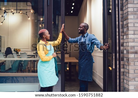 Joyful business partners in uniform looking at each other and giving high five while standing on entrance of own cafe and celebrating successful start Foto d'archivio ©