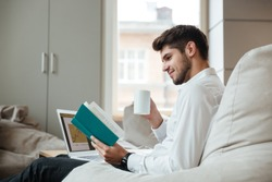 Joyful businessman dressed in white shirt sitting in cafe and drinking tea while sitting near at laptop and reading book.