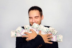 Joyful businessman. The money fell into the hands. armful of money in the hands of a young entrepreneur. Rubles in packs. Million rubles. The winner of the lottery.