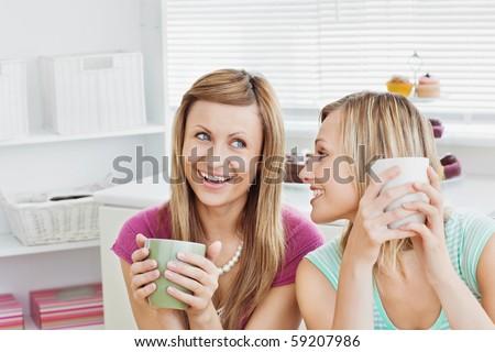 Joyful caucasian friends drinking coffee after baking in the kitchen