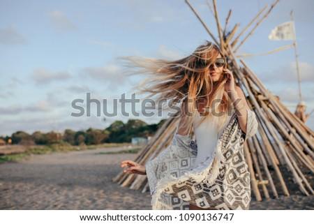 Joyful caucasian girl in summer attire chilling at beach. Pretty long-haired female model in sunglasses having fun at resort in windy day.
