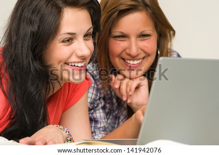 Joyful caucasian teens browsing on internet