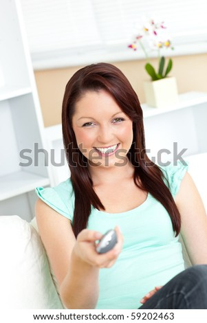 Joyful caucasian woman holding a remote smiling at the camera in the living-room