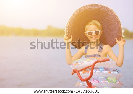 Joyful child enjoys a holiday in the water with swimming rings. Joy of freedom and life. #1437160601