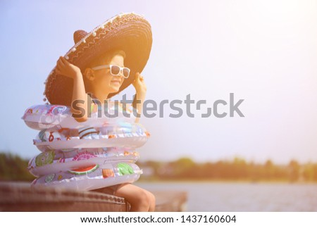 Joyful child enjoys a holiday in the water with swimming rings. Joy of freedom and life. #1437160604