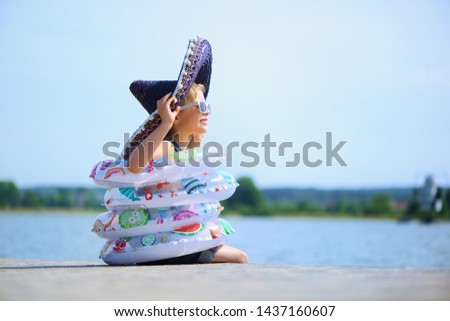 Joyful child enjoys a holiday in the water with swimming rings. Joy of freedom and life. #1437160607