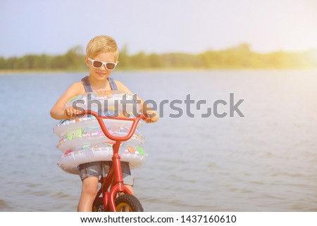 Joyful child enjoys a holiday in the water with swimming rings. Joy of freedom and life. #1437160610