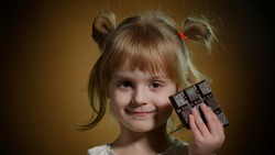 Joyful child kid with chocolate bar showing ok gesture sign. Lovely teen girl making faces, smiling, satisfactorily nods her head. Addiction of sweets and candies. Advertising of product