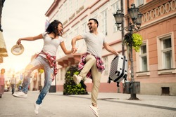 Joyful couple enjoying walking at street. Find your travel partner.