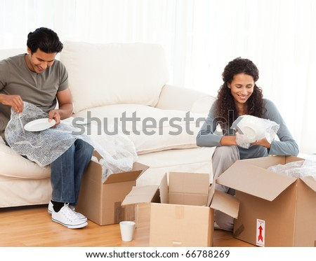 Joyful couple packing glasses together in the living room for their new house