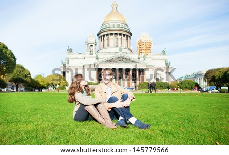 Joyful couple sitting on the grass near St. Isaac's cathedral