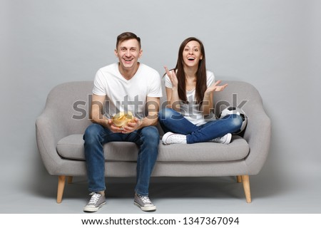 Joyful couple woman man football fans cheer up support favorite team with soccer ball, holding glass bowl of chips isolated on grey background. People emotions, sport family leisure lifestyle concept Photo stock ©