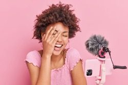 Joyful curly Afro American woman influencer laughs happily keeps hand on face has funny conversation with subscribers poses against pink backgroud. Socal media blogging and technology concept